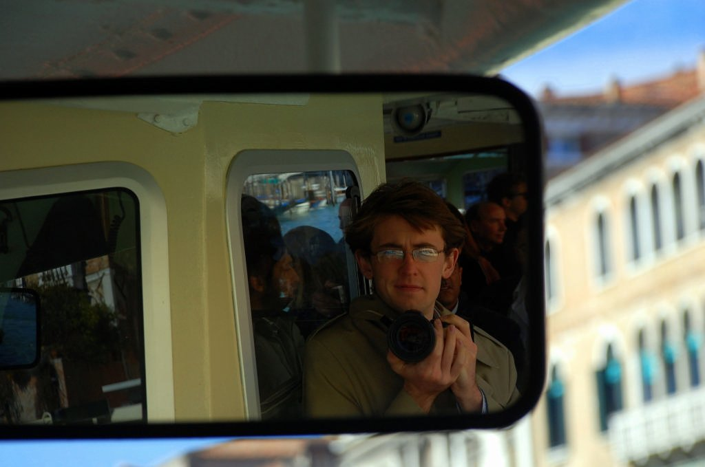Ross Heintzkill stands facing a rearview mirror with Venice's canals behind him