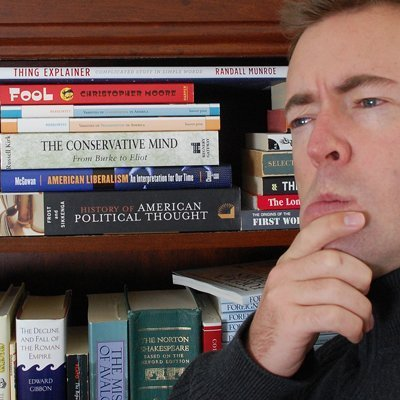 Ross Heintzkill seated in front of a bookshelf, pondering something -- we know not what