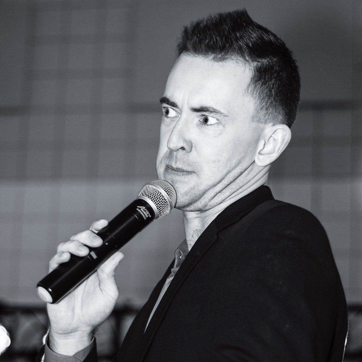 Ross Heintzkill, circa 2015, emceeing an event and holding a microphone. A perfectly odd moment captured by the photographer.
